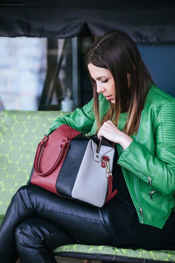 Modeflickan söker efter något i hennes handväska arkivfoto