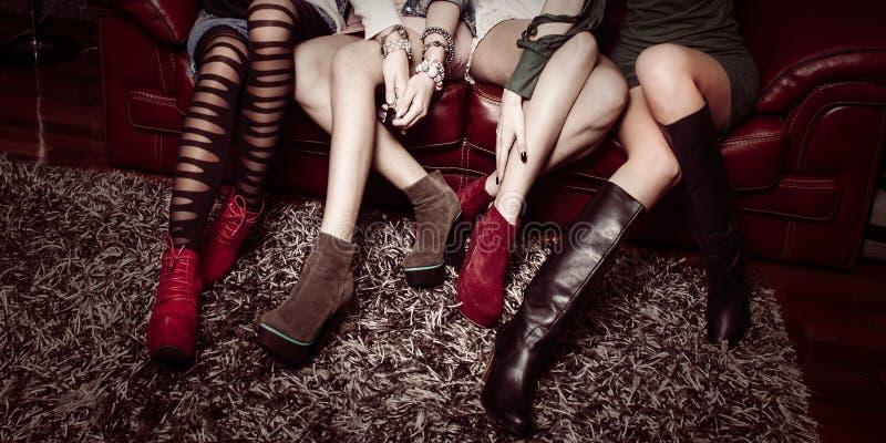 Modeflickor och deras skor arkivfoto