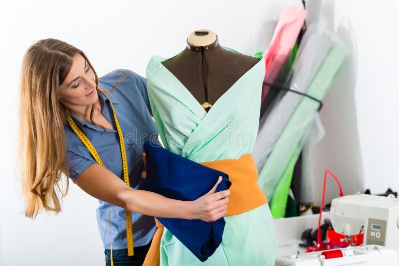 Modeformgivare eller skräddare som arbetar i studio arkivfoton