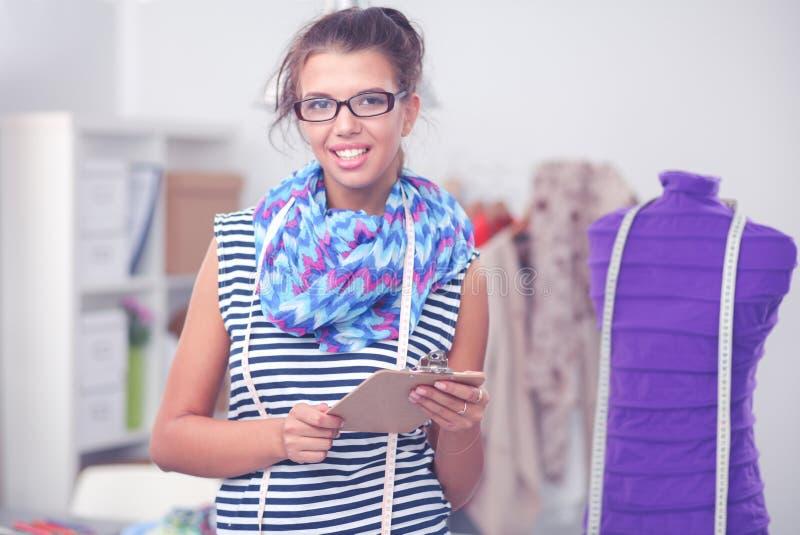 Modeformgivare f?r ung kvinna som arbetar p? studion royaltyfri fotografi