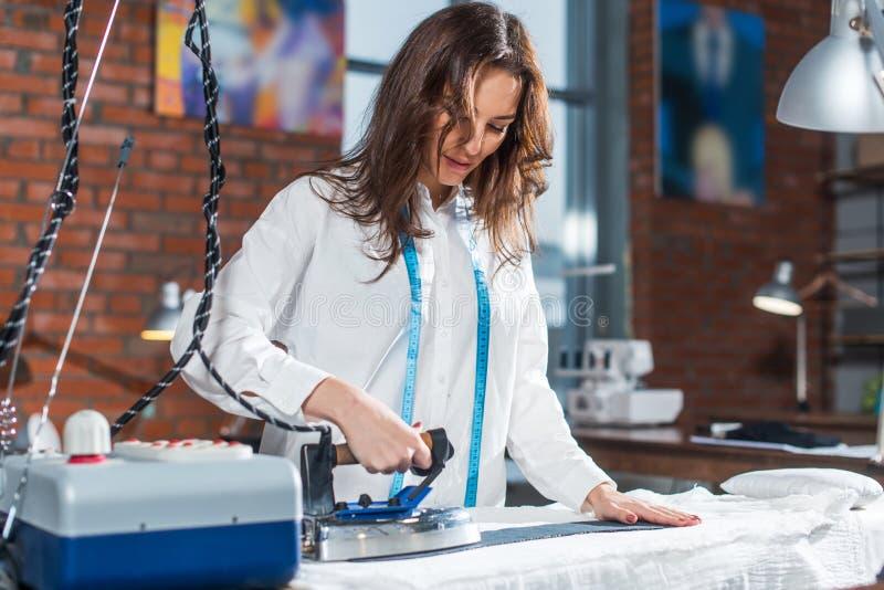 Modeformgivare som använder ångajärn för att trycka på torkduken som arbetar i studio arkivfoton