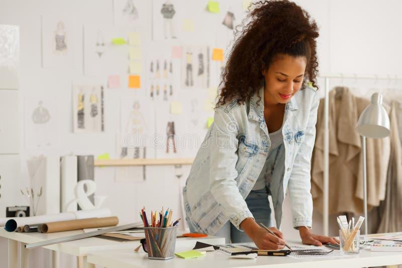Modeformgivare som arbetar i atelier royaltyfri bild