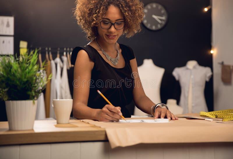 Modeformgivare som arbetar på hennes atelier royaltyfria foton