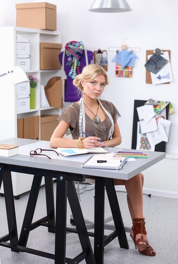 Modeformgivare som arbetar p? hennes designer i studion arkivbilder