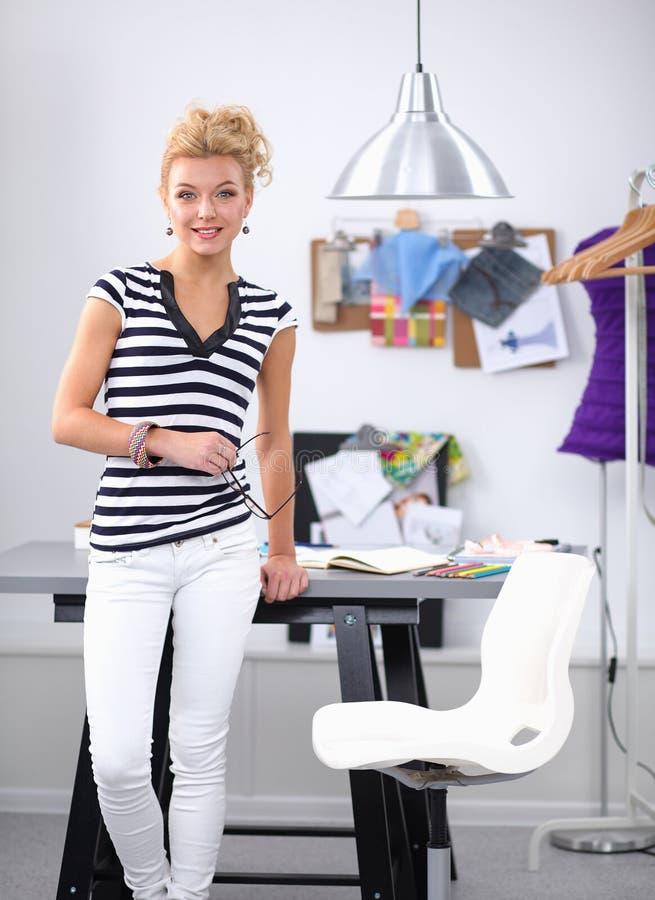Modeformgivare som arbetar p? hennes designer i studion arkivbild