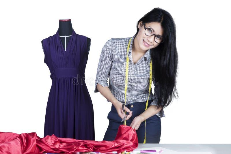 Modeformgivare som klipper ett tyg på studio royaltyfria foton