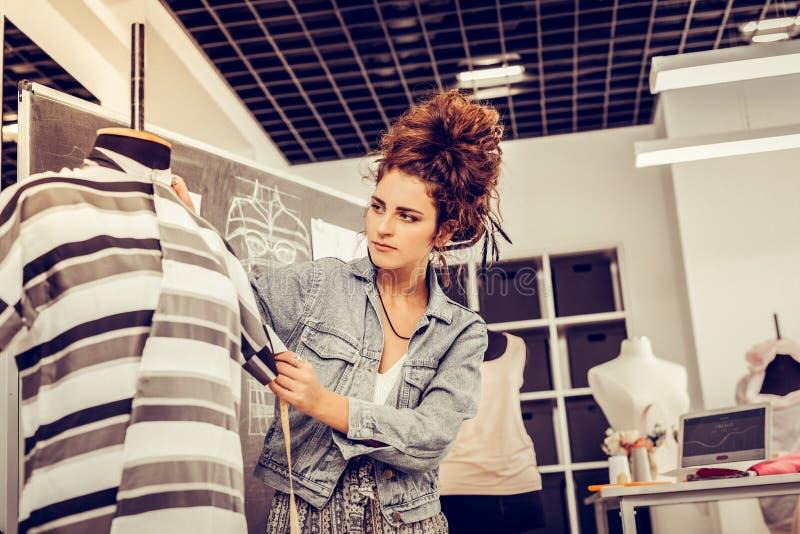 Modeformgivare som mäter försiktigt hennes nya skapelse arkivbild