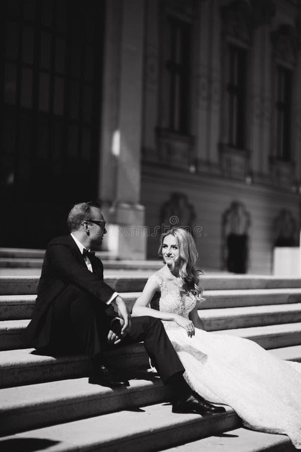 Modefoto av att gifta sig par Brudgummen bär den blåa dräkt- och bandpilbågen Bruden bär den vita bröllopsklänningen svart white royaltyfria bilder