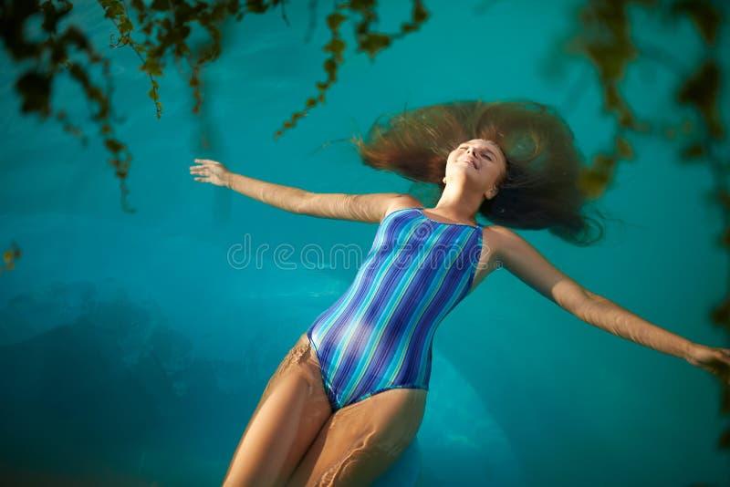 Modefoto av den attraktiva slanka kvinnan med långt blont hår i elegant randig kroppbaddräkt som kopplar av i simbassäng royaltyfri foto