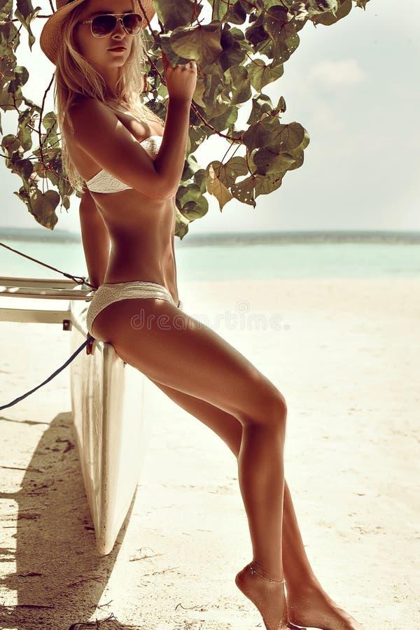Modefoto av den härliga brunbrända kvinnan med blont hår i elegant vit bikini som kopplar av på den vita sandstranden royaltyfria foton