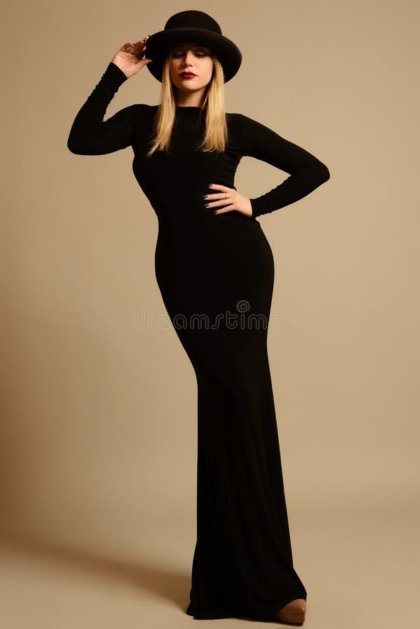 Modefoto av den härliga damen i elegant svart klänning och hatt royaltyfri bild