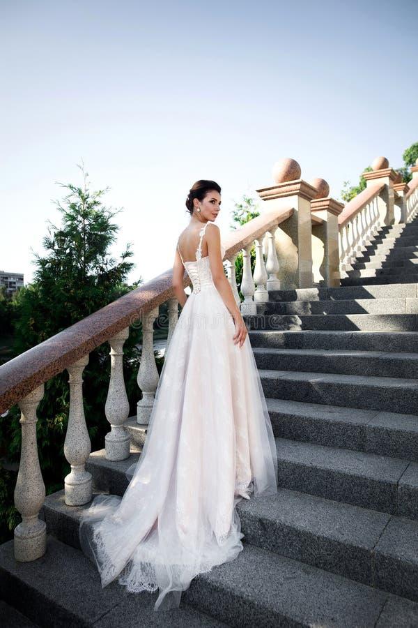Modefoto av den härliga kvinnan, i att posera för bröllopsklänning som är utomhus- fotografering för bildbyråer
