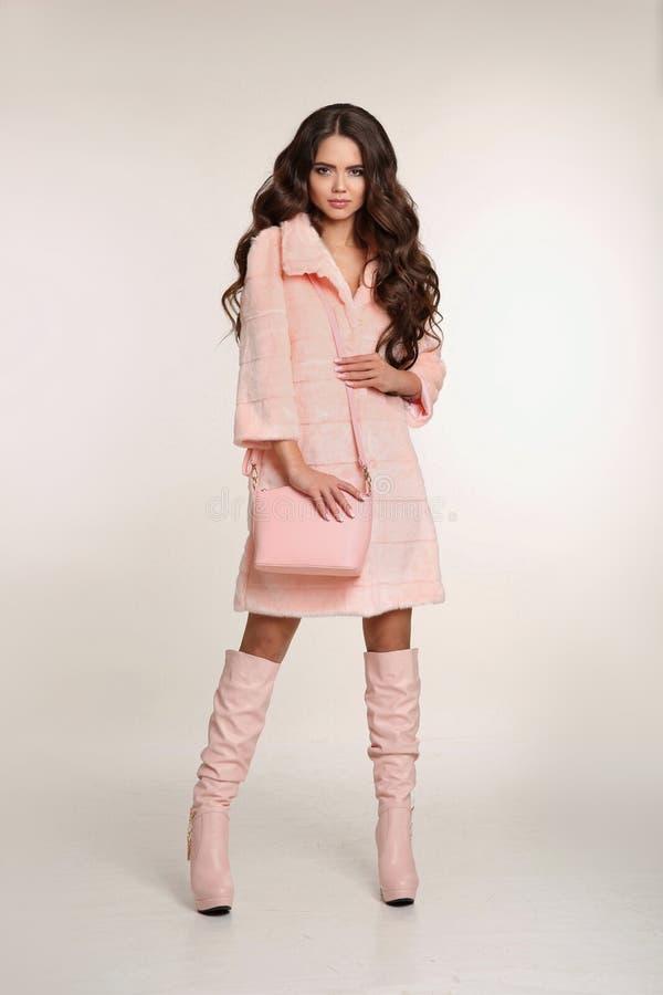 Modefoto av den trendiga kvinnan i rosa färglag med handväskawea arkivfoto