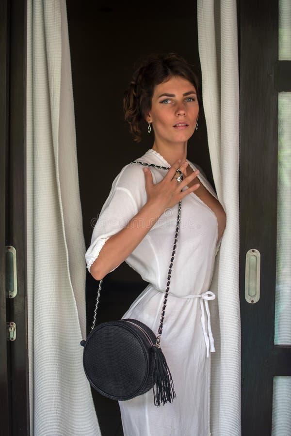 Modefoto av den ursnygga sinnliga kvinnan med krabbt hår för lång brunett, i lyxigt vitt anseende och att posera för udde mot sva royaltyfri bild