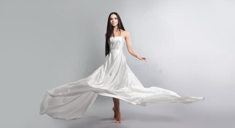 modefoto av unga flickan i det vita klänningflygsilkespappret Lättvikts- material royaltyfri bild