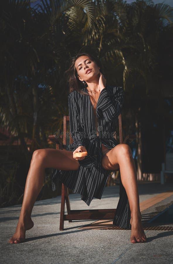 Modefoto im Freien junger schöner Dame am Luxuslandhaus Frauenholdingstück von Ananas Sommerschwingungen lizenzfreies stockbild
