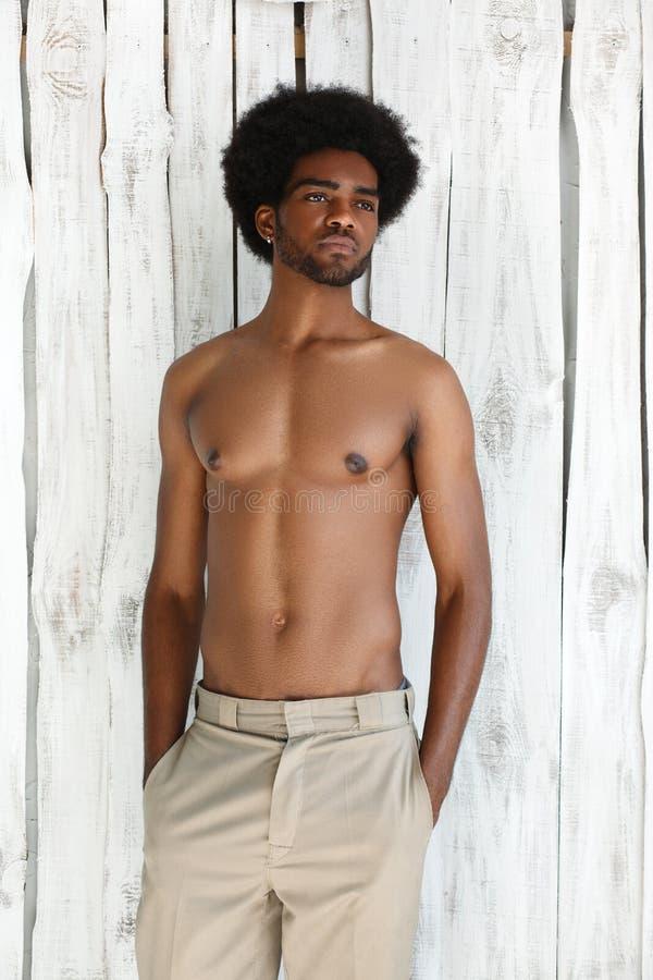 Modefotoet av den idrotts- mannen för afrikanska amerikanen med den våta kroppen för sporten poserar nära texturväggbakgrunden arkivbilder