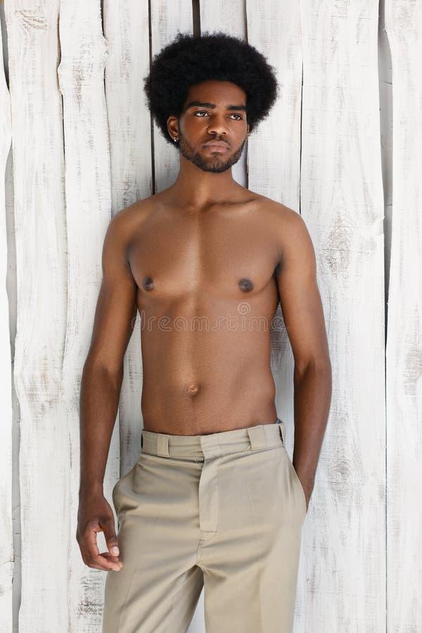 Modefotoet av den idrotts- mannen för afrikanska amerikanen med den våta kroppen för sporten poserar nära texturväggbakgrunden royaltyfria bilder