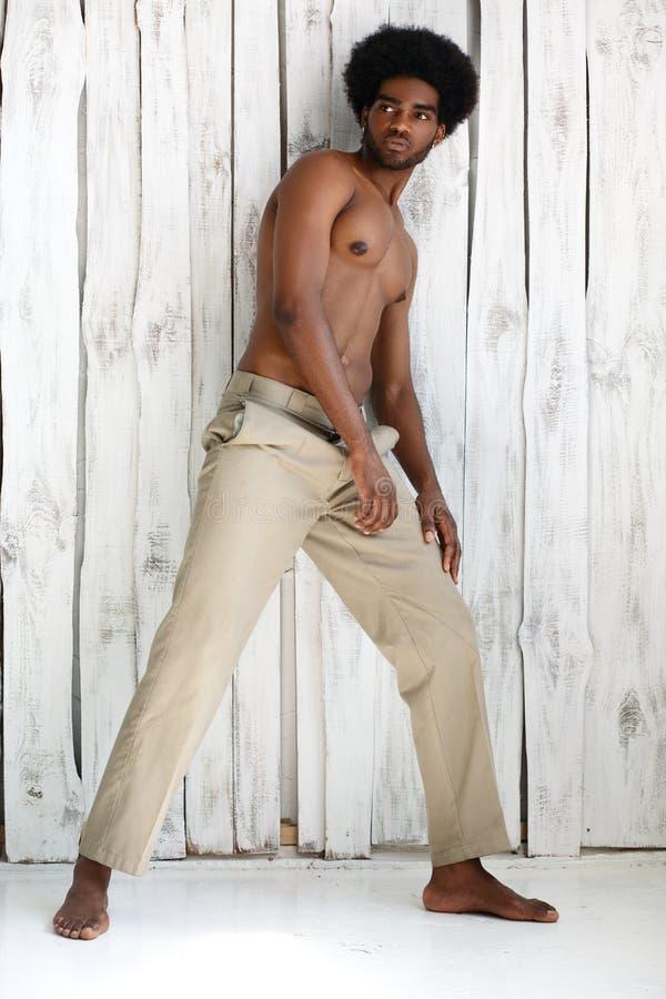 Modefotoet av den idrotts- mannen för afrikanska amerikanen med den våta kroppen för sporten poserar nära texturväggbakgrunden royaltyfria foton