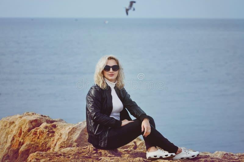 Modefrau, die nahe dem Meer sich entspannt stockbilder