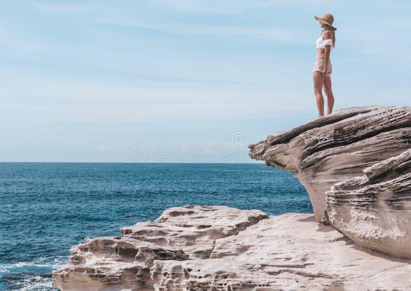 Modefrau, welche die Sommersonne durch die Küste genießt stockfotografie
