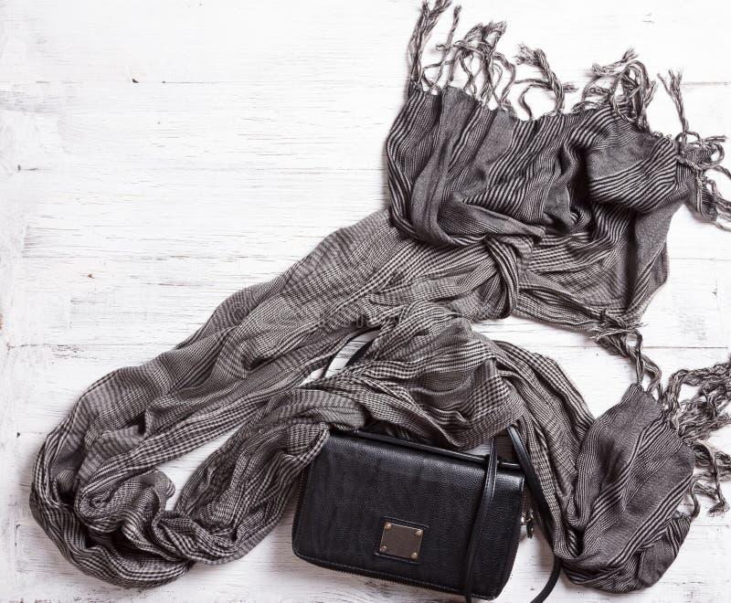 Modefrauenzubehör Lederne schwarze Handtasche und grauer Schal stockfoto