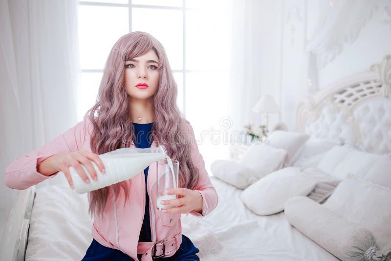Modefreak Synthetisches Mädchen des Zaubers, gefälschte Puppe mit leerem Blick und langes lila Haar gießt Milch in das Glas lizenzfreie stockfotografie