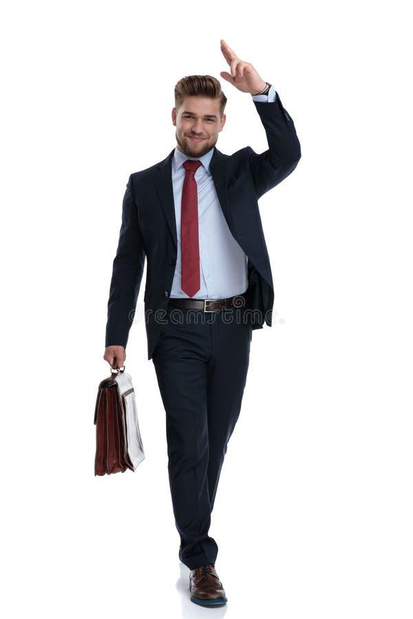 Modegeschäftsmann, der seinen Aktenkoffer tritt und hält lizenzfreie stockfotos