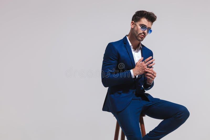 Modegeschäftsmann in der Sonnenbrille ist, halten sitzend und Palmen t lizenzfreies stockfoto