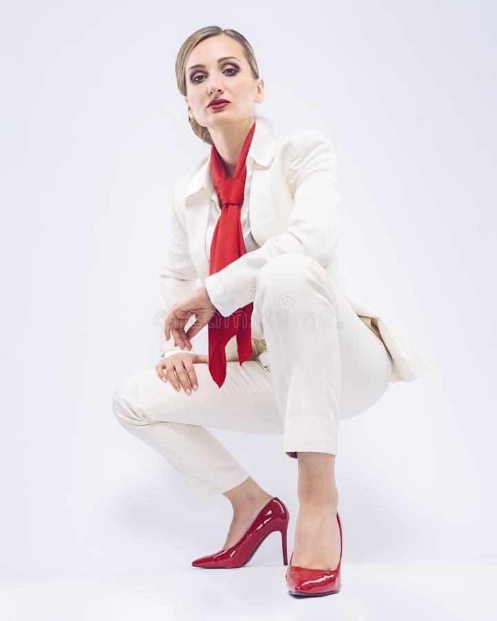 Modegeschäftsmodell, das einen weißen Anzug und roten Zusätze trägt stockbild