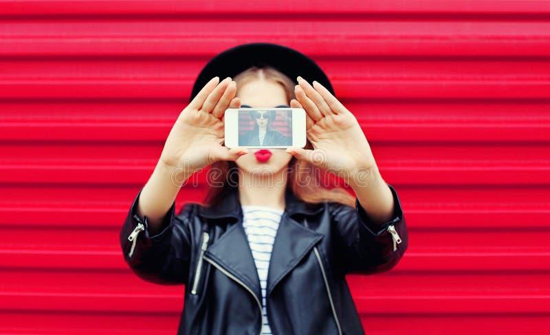 Modeglamourkvinnan gör självståenden på smartphonen som blåser kanter över stadsrosa färger arkivbilder