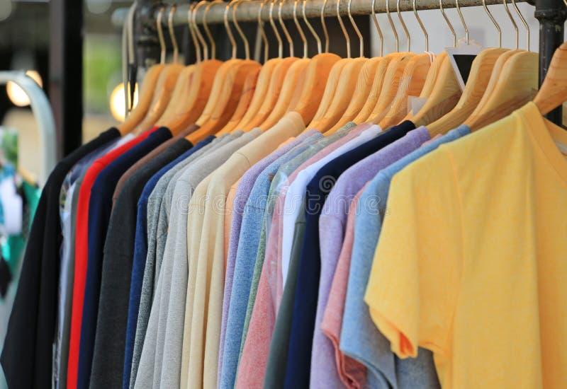 Modekläder hänger på den till salu kläderkuggen royaltyfria foton
