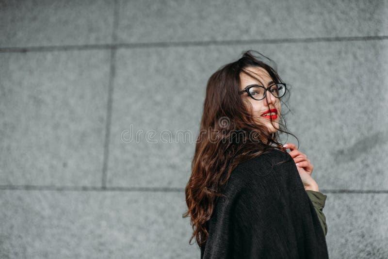 Modekonzept: schönes junges Mädchen mit dem langen Haar, den Gläsern, den roten Lippen, die nahe der modernen Wand trägt im grüne lizenzfreies stockfoto