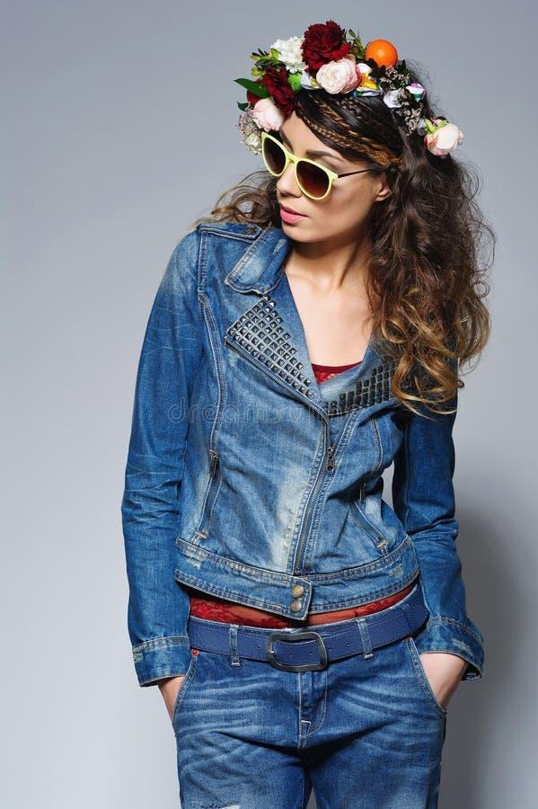 Modekvinna i jeans dräkt och solglasögon arkivbilder