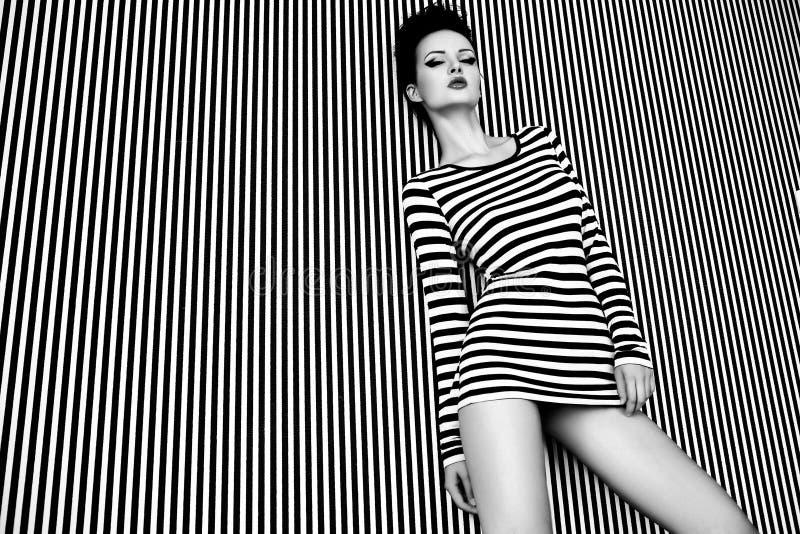 Modekvinna i randig klänning på randig bakgrund i studio royaltyfria bilder