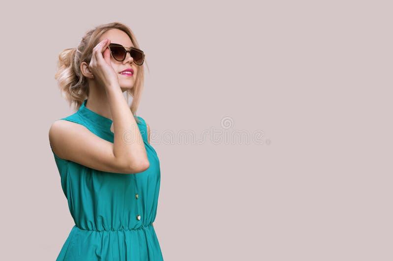 Modekvinna i solglasögon på en grå bakgrund royaltyfri bild