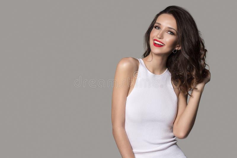 Modekvinna i vita klänningskratt Röd läppstift och härlig makeup royaltyfria bilder