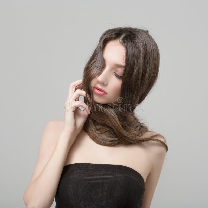 Modekvinna med härligt långt hår Att bry sig för en kvinna med ett härligt smink royaltyfri bild