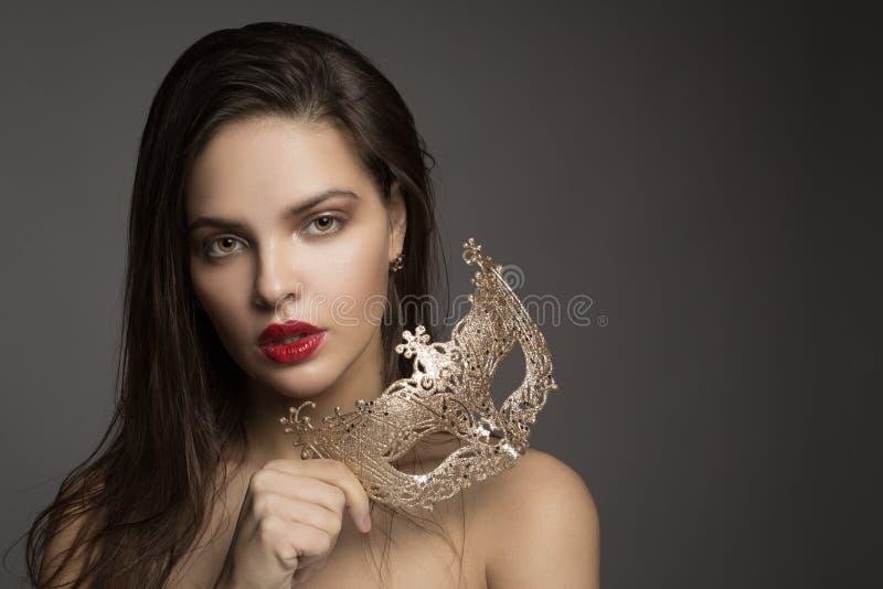 Modekvinna med långt hår och röd läppstift med den guld- maskeringen royaltyfria foton