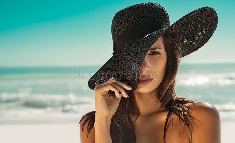 Modekvinna med sugrörhatten på stranden arkivbild