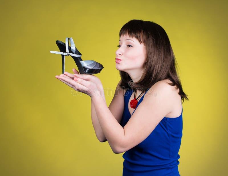 Modekvinna som kysser enhäl sko Kvinnaförälskelse skor begrepp Skor för lycklig flicka och för höga häl på gul bakgrund härligt royaltyfri foto