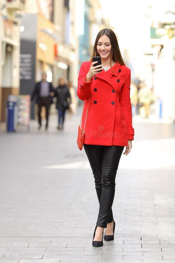 Modekvinna som smsar en smart telefon i vinter royaltyfria foton