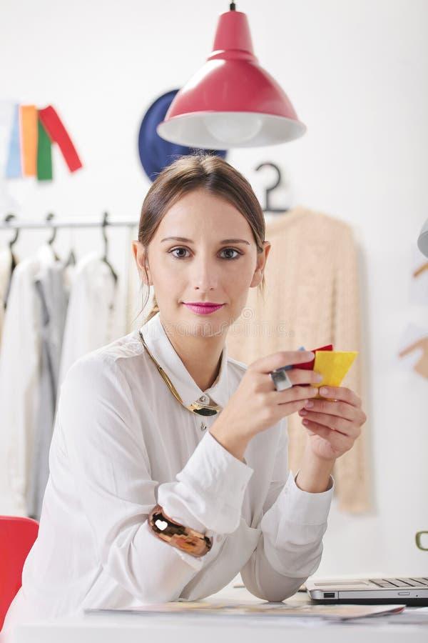Modekvinnablogger i en idérik workspace som väljer färger. arkivfoton