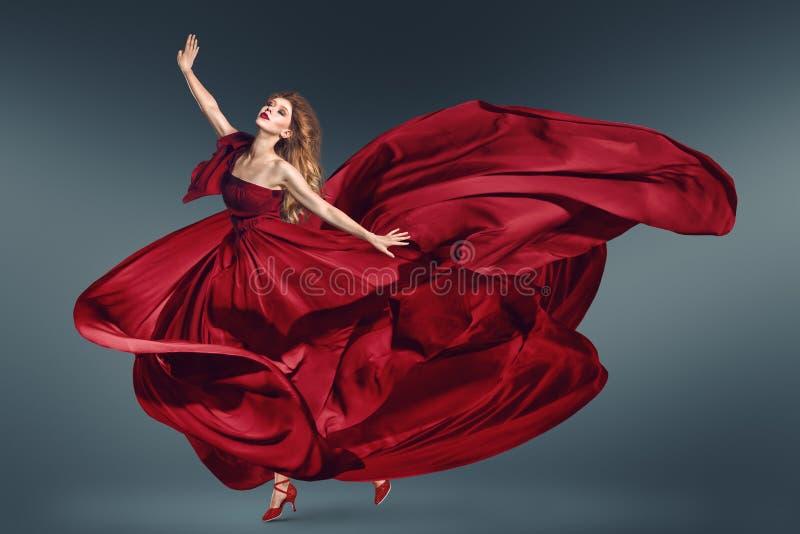 Modekvinnadans, i att fladdra den röda klänningen royaltyfria foton