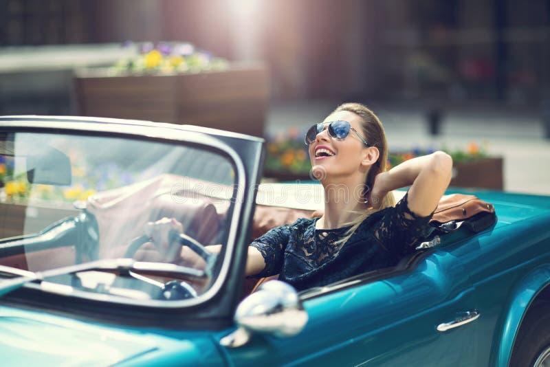 Modekvinnamodell i solglasögon som sitter i lyxig bil arkivfoton