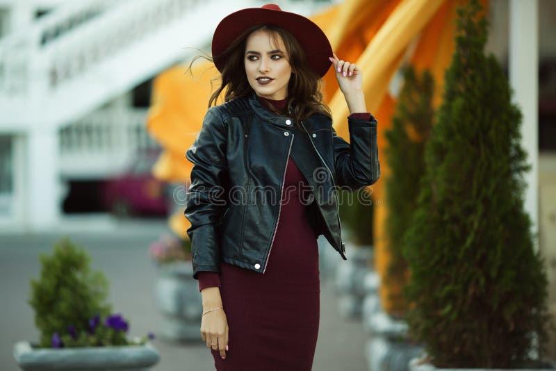 Modekvinnan bär den varma modehöstkläder och hatten i framdel som går i centret, stads- stil arkivbild