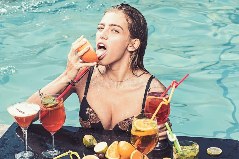 Modekvinnan med f?rnyar alkohol i miami Bantar ny vitaminfruktsaft f?r drinken, P?lparti att koppla av i brunnsortsemesterort Som royaltyfri fotografi