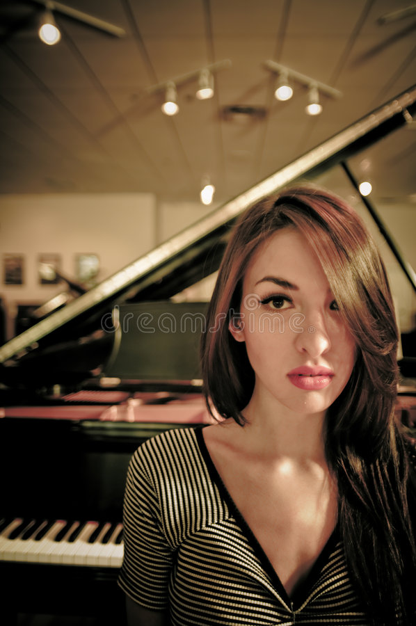 Model. Young female model in a piano store royalty free stock image