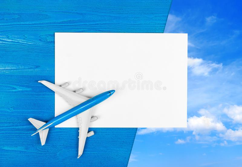 Model of airplane and blank sheet of paper on the blue wooden background. Travel concept. stock images