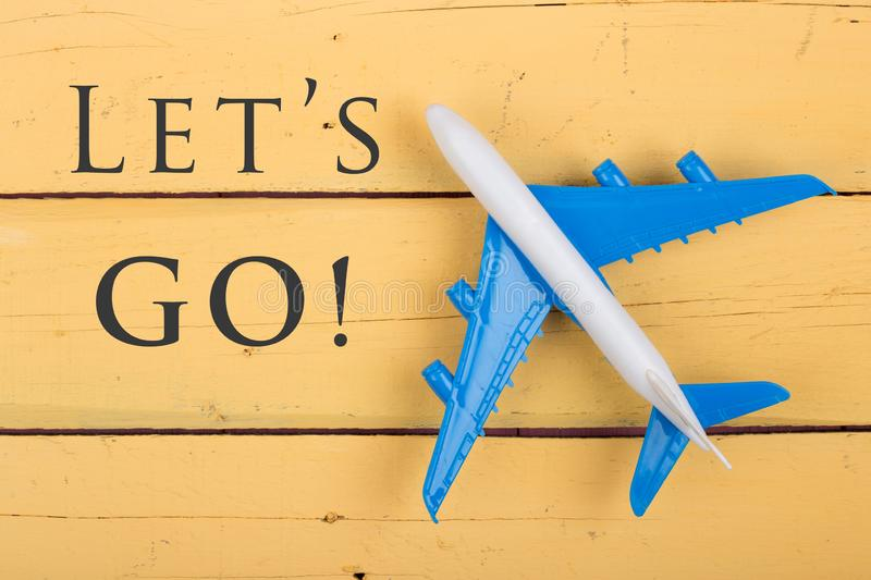 Model of airplane and text Let's go! on yellow wooden background. Top view, lets, travel, toy, aerial, aircraft, aviation, blue, child, close, up, desk royalty free stock photo